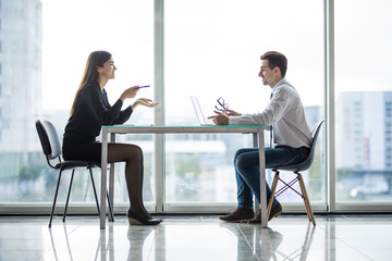 Businessman And Businesswoman Meeting In Modern Office face to face discuss plans