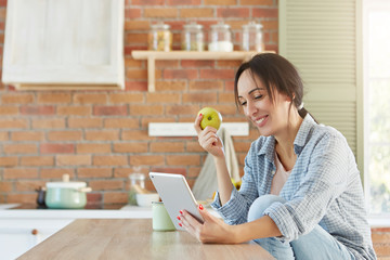 Healthy food and lifestyle concept. Pretty female eats apple, looks for new diet in internet, uses tablet computer, being glad to loose weight. Woman watches film on kitchen as dinner is prepared