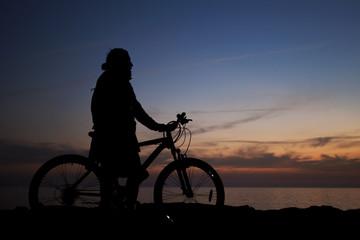 gün batımını izleyen bisikletli adam