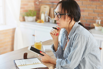 Beautiful female model with dark pony tail, dressed casually, uses modern digital tablet, counts calories, makes notes in notepad as sits in cozy kitchen. Businesswoman works during weekends at home
