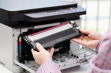Man replacing toner in laser printer