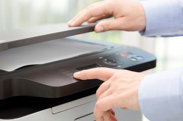 Hand press button on panel of printer