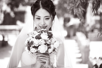 happy asian bride with flowers