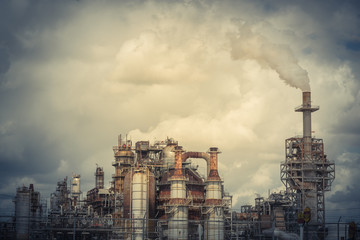 Oil refinery, oil factory, petrochemical plant in Pasadena, Texas, USA. Air pollution from smoke stacks under cloudy sky. Vintage tone.