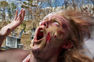 A grotesque and bloody female zombie in a grave yard