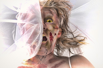 Grotesque and bloody female zombie's face in partially covered by a delicate lace wedding veil