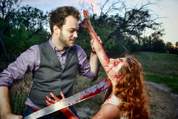 A mans is about to behead a grotesque and bloody female zombie in a wooded area