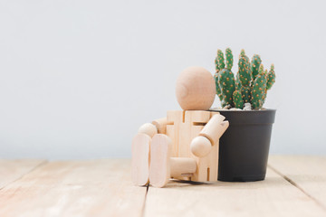 Wooden mannequin sitting back relax on side cactus pot, on wooden floor