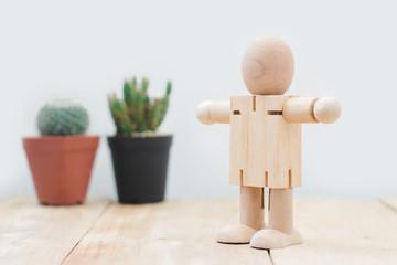 Wooden mannequin standing relax on side cactus pot, on wooden floor