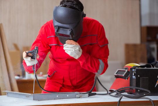 Young repairman with a welding gun electrode and a helmet weldin