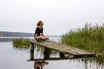 Girl with a sports sexy figure is engaged in sports yoga stretching fitness on background of a calm autumn river lake. Girl is reflected in water. Meditation, relaxation, balance, calmness.
