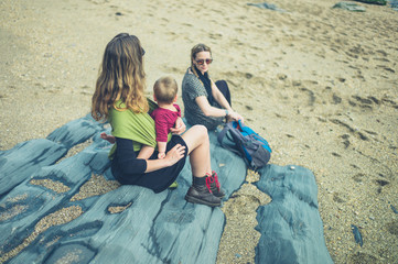Two women with a baby sitting on the beach