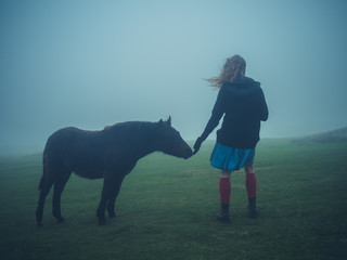 Woman petting a wild pony