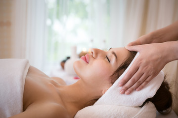 Happy of relaxing beautiful young woman receiving facial massage with closed eyes in a spa salon