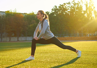 sports girl doing morning gymnastics workout on green grass. In the control of warm sunlight. Fitness, sport, health, energy.