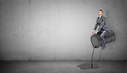 A small businessman sits on a black barrel leaking oil like on a horse.