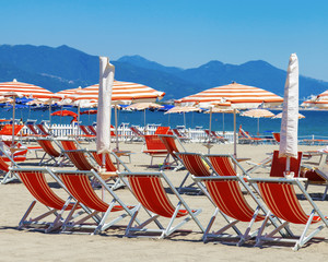 Summer beach of Italy, Ligurian coast of Italy in province of La Spezia. Red sun umbrellas and red beds.