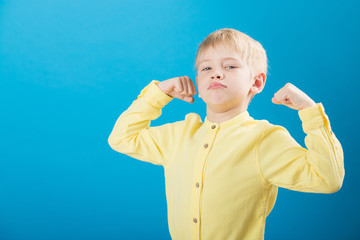 Charming small caucasian boy showing muscle on yellow background