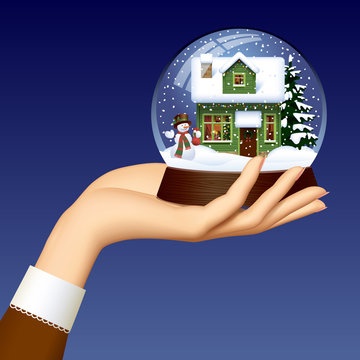 Woman's hand holding a Xmas snow globe with snowman, green wooden house covered with snow