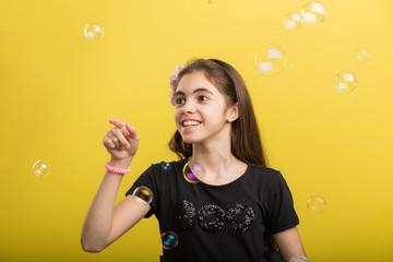 little Girl having fun with bubbles on studio