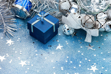 christmas tree decorations on blue sparkling background. silver balls, drum and blue small gift box.