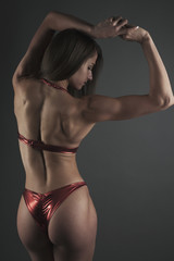 sport woman bikini back studio shot on dark bg
