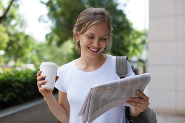 Positive Woman Reading Newspaper on Street