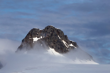 A mountain top reaches over the mist and clouds in Antarctica.
