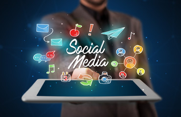 Businessman holding tablet with social media graphics