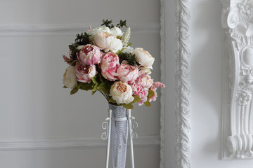 bouquet of peonies in vase against white wall in photo studio