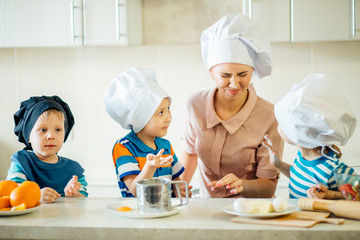 happy family in the kitchen. mother and children preparing dough, bake cookies