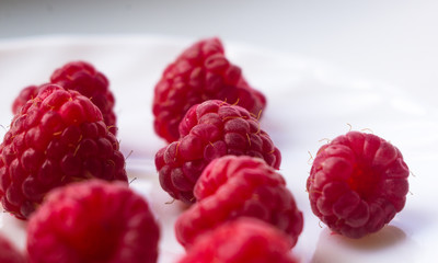 raspberries on a white saucer close up