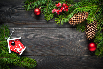 Christmas background with fir tree and decorations at dark wooden table.