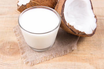 Coconut with coconut milk on wooden background.