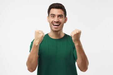 Soccer fan in green t-shirt celebrating win of his team, screaming,  isolated on gray background