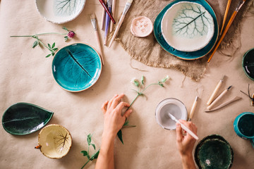 Obraz Woman painting clay pot with senior potter at workshop - fototapety do salonu