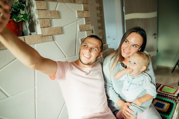 happy family sitting on couch and making selfie with smartphone
