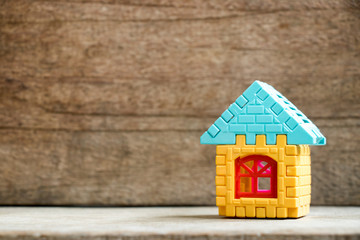 Puzzle model in home shape on wood background