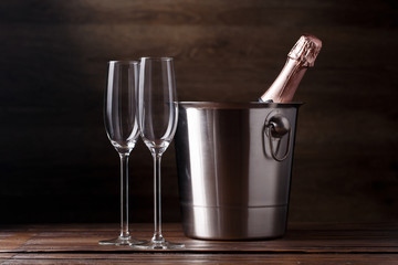 Photo of two empty wine glasses, iron bucket