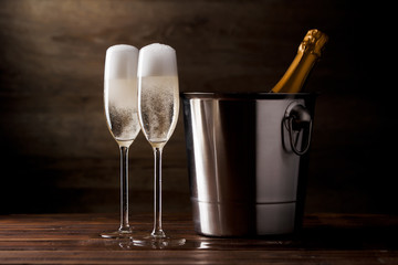 Photo of two glasses with sparkling wine, iron bucket