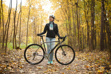 Image of girl in helmet, jeans next to bicycle in autumn park