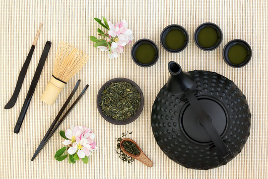 Japanese sencha sukiygu makoto tea ceremony with equipment including oriental teapot, cups, whisk, stick stirrers, tongs, tea leaves and spring blossom on bamboo background.