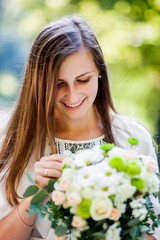 Stunning woman in dress with flowers stands in the garden