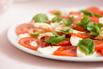 Tomato and mozzarella salad with basil leaves, sprinkled with pepper, olive oil and acceto balsamico on the white plate