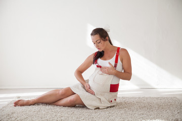 a pregnant woman sitting on the floor talking with a baby in the belly