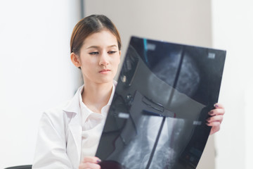 Thoughtful female doctor looking at the Mammogram film image.