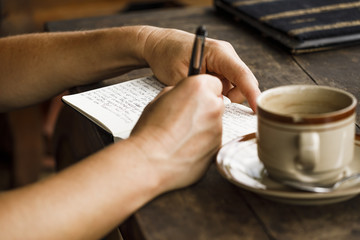 Frau schreibt Tagebuch - mit Kaffee