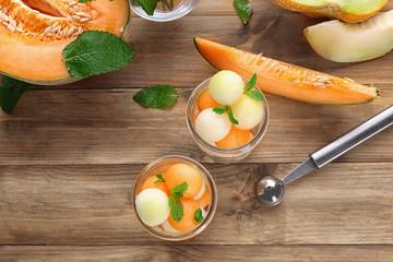Jars with fresh melon balls on table