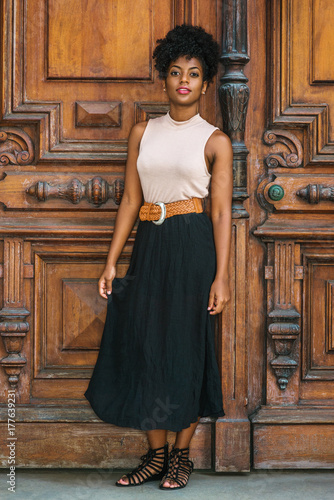 2c51e268194 Young black female teacher with afro hairstyle wearing sleeveless light  color top, black skirt, strappy sandals, standing by vintage office door.