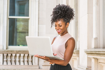 Way to Success. Young African American woman with afro hairstyle wearing sleeveless light color top, standing in vintage office building in New York, looking down, working on laptop computer, smiling.